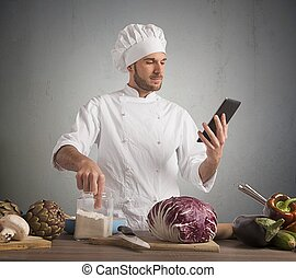 Cook with technology - Chef reads a recipe from the tablet