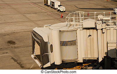 Jetway Over Tarmac - An empty jetway on tarmac at a busy...