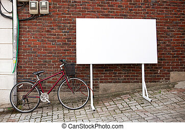 Blank advertisement board at street with bicycle next to it...
