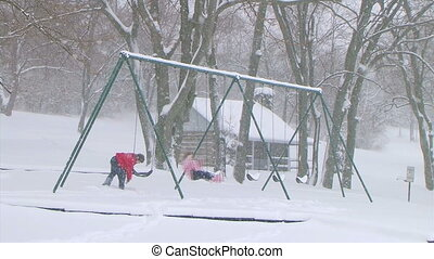 Girl Swinging in Snow - Boy pushing girl on swing during...