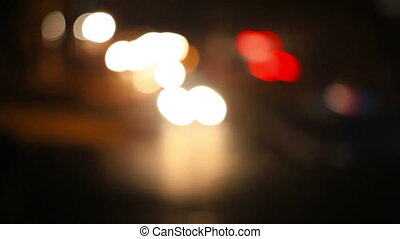 Out of focus city traffic at night. Car headlights and tail...