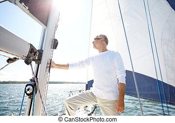 senior man on sail boat or yacht sailing in sea - sailing,...
