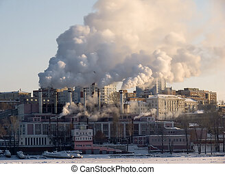 Winter urban landscape. From pipe factory fells smoke into...