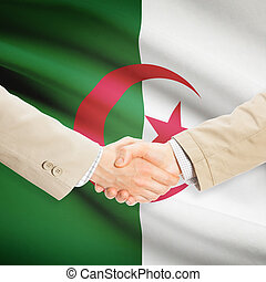Businessmen handshake with flag on background - Algeria -...