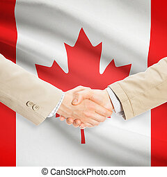 Businessmen handshake with flag on background - Canada -...