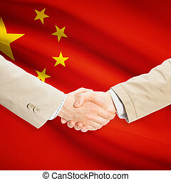 Businessmen handshake with flag on background - People's...