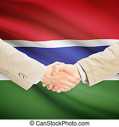 Businessmen handshake with flag on background - Gambia -...