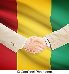 Businessmen handshake with flag on background - Guinea -...