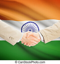 Businessmen handshake with flag on background - India -...