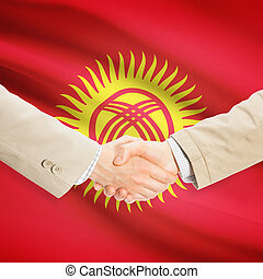 Businessmen handshake with flag on background - Kyrgyzstan -...