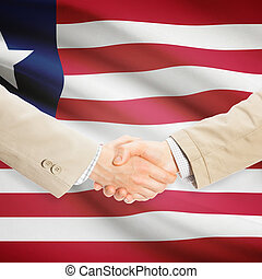 Businessmen handshake with flag on background - Liberia -...