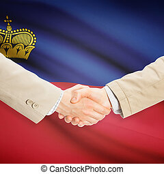 Businessmen handshake with flag on background -...