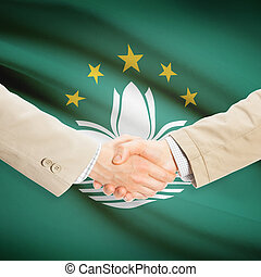 Businessmen handshake with flag on background - Macau -...