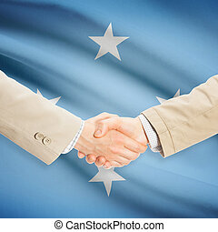 Businessmen handshake with flag on background - Micronesia -...