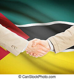 Businessmen handshake with flag on background - Mozambique -...
