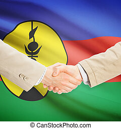 Businessmen handshake with flag on background - New...