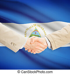 Businessmen handshake with flag on background - Nicaragua -...