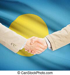Businessmen handshake with flag on background - Palau -...