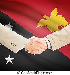 Businessmen handshake with flag on background - Papua New...