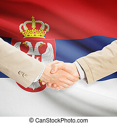 Businessmen handshake with flag on background - Serbia -...