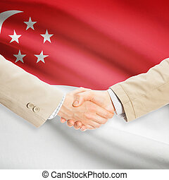 Businessmen handshake with flag on background - Singapore -...