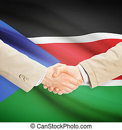 Businessmen handshake with flag on background - South Sudan...