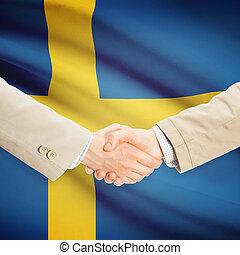 Businessmen handshake with flag on background - Sweden -...