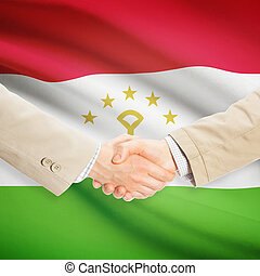 Businessmen handshake with flag on background - Tajikistan -...