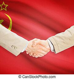 Businessmen handshake with flag on background - USSR -...