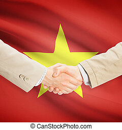 Businessmen handshake with flag on background - Vietnam -...