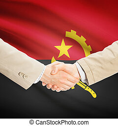 Businessmen handshake with flag on background - Angola -...