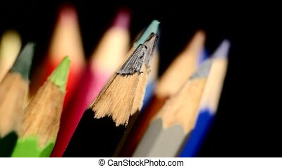 Different colour pencils isolated on black, rotation, close...