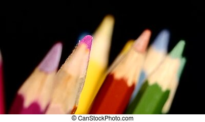 Top of different colour pencils isolated on black, rotation,...