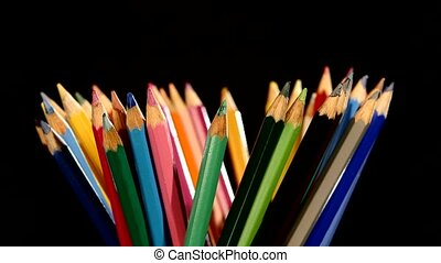 Colour pencils isolated on black, rotation