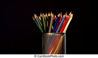 Colour pencils in box isolated on black, rotation - Many...