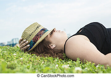 Profile view of woman relaxing on grass