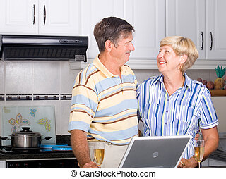 happy senior couple - a happy senior couple in kitchen with...