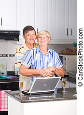 modern senior lovers embracing in kitchen with laptop on...