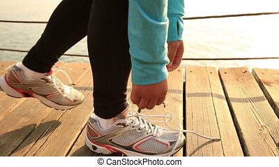 sports woman runner tying shoelace - young sports woman...