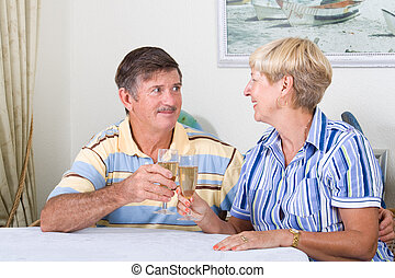 celebrating couple - a celebrating senior couple toasting...