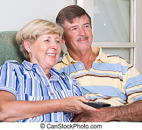 senior couple watching tv - a happy senior couple watching...