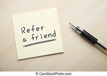 Refer a friend - Text Refer a friend written on the sticky...