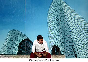 Young Indian business man talks on a smartphone - One young...