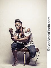 Poor Strong Young Man on a Chair Clenching Fist - Poor...