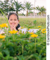 A cute girl lie down on a field behind yellow flowers