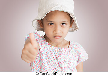 little girl showing thumb up isolated on pink background