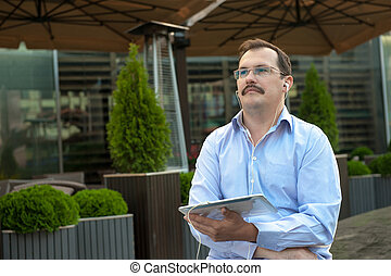 Man using tablet computer outdoors