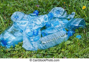 Plastic bottles and bottle caps on grass in park, littering...