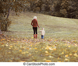 Mother and child walking together in autumn park, life moment