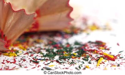 Different crayon shavings on white, close up, slow motion -...